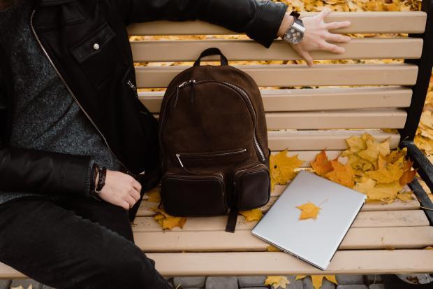 рюкзак и книга на скамейке рядом с мужчиной