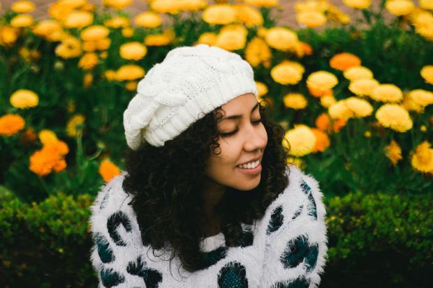 девушка в свитере и берете сидит возле клумбы с яркими цветами