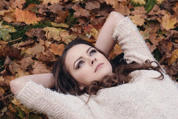 девушка в свитере лежат на осенней листве
