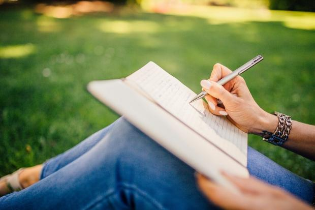 девушка в синих джинсах пишет в дневнике