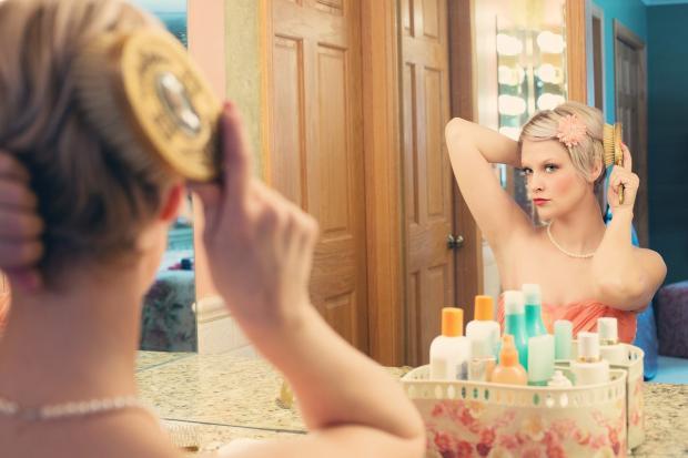 девушка причесывается перед зеркалом