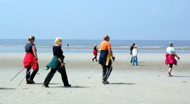 люди идут по пляжу скандинавской ходьбой