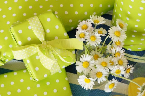 завязанные зеленой в горошек бумагой подарки лежат рядом с ромашками