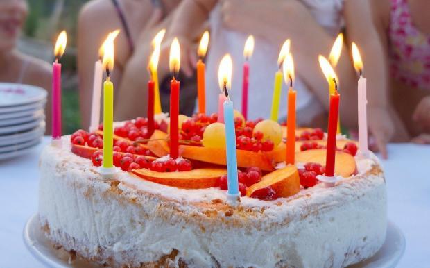 цветные свечи горят на праздничном торте