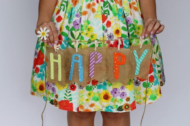 девочка в цветастом платье держит табличку со словами день рождения