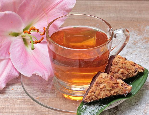 прозрачная чашка с чаем стоит на блюдце с печеньем