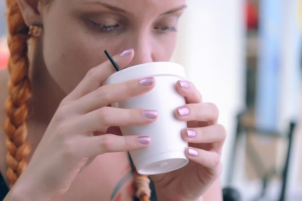 девушка пьет чай из белого стакана