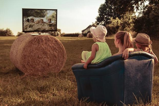 мама с лочками сидя в кресле смотрят в поле телевизор установленный на рулон соломы