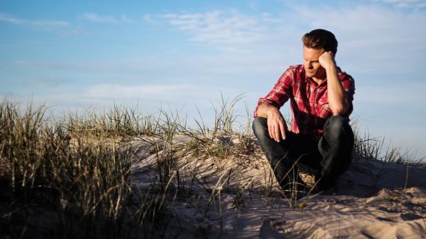 грустный мужчина в красной рубашке сидит на берегу реки