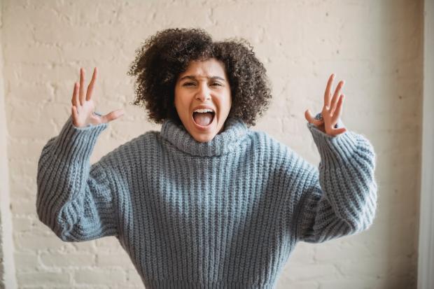 кудрявая девушка в свитере подняла руки от злости