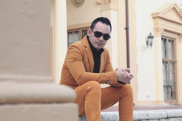 молодой парень в костюме сидит на ступеньках