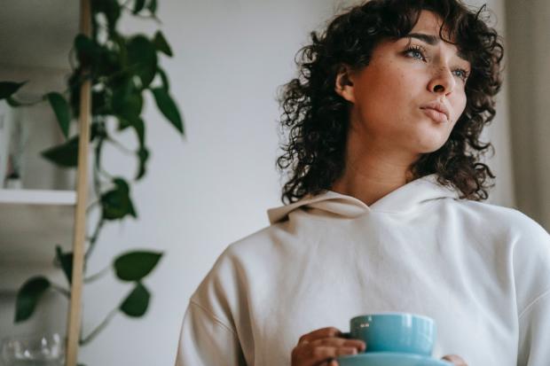 девушка с чашкой смотрит в окно