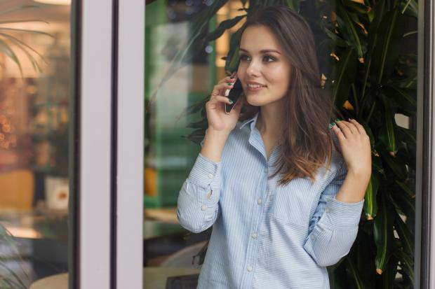 девушка в рубашке с телефоном