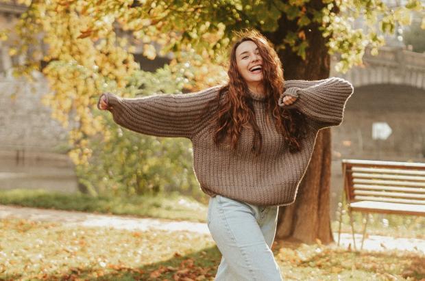 девушка в свитере и с распущенными волосами танцует на осенней аллее