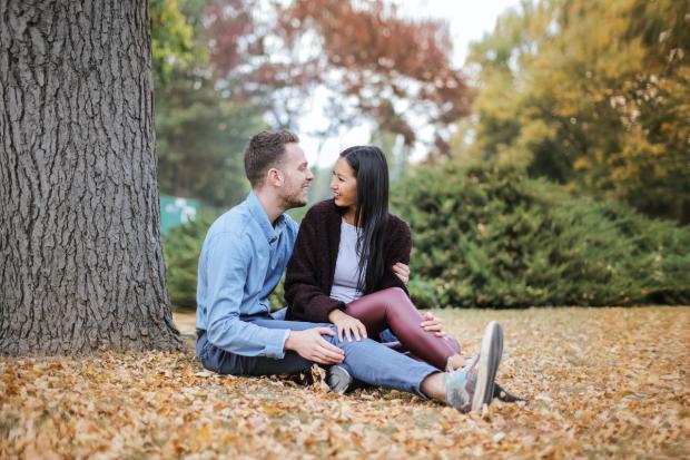 влюбленные сидят на усыпанной осенней листвой земле под деревом